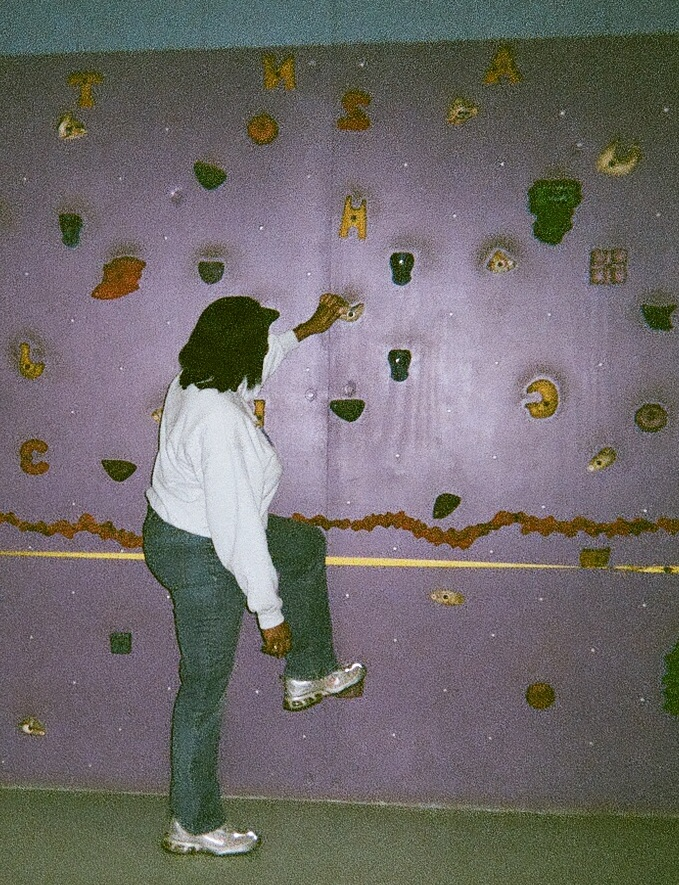 Kim Hopkins demonstrates rock climbing in a physical education class for kids