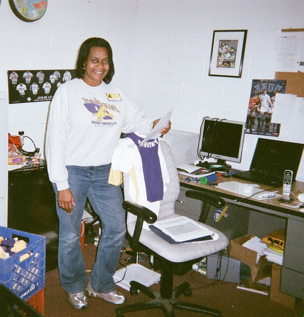 Kim Hopkins, a substitute teacher, standing in an elementary school gym office