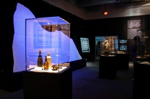 The freezing cold iceberg stands in night light behind an enclosed exhibit of glassware from the Titanic.